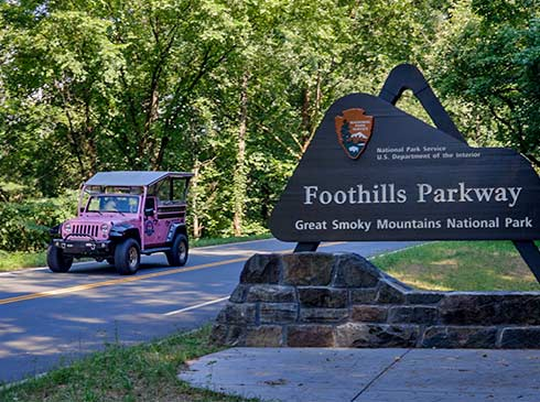 Pink Jeep driving past Foothills Parkway entrance sign, Great Smoky Mountains, TN