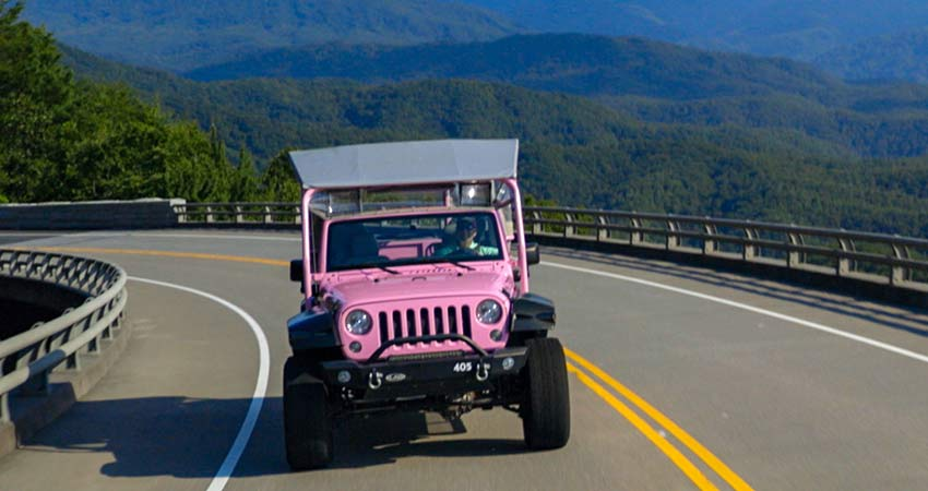 Pink Jeep Wrangler driving towards camera on Foothills Parkway bridge, with scenic view of Smoky Mountains in background