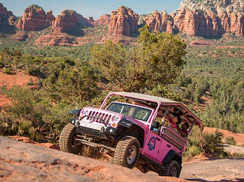 A customized Pink® Jeep® navigates Sedona's rugged desert terrain on the Broken Arrow tour