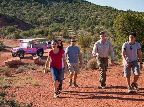 Pink® Jeep® guide and family of four walking up hill to Mystic Mesa on the tranquil Touch the Earth tour