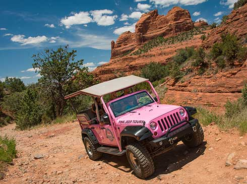 A custom-built, open-air Pink® Jeep® climbs Schnebly Hill Road through Sedona's rugged backcountry.