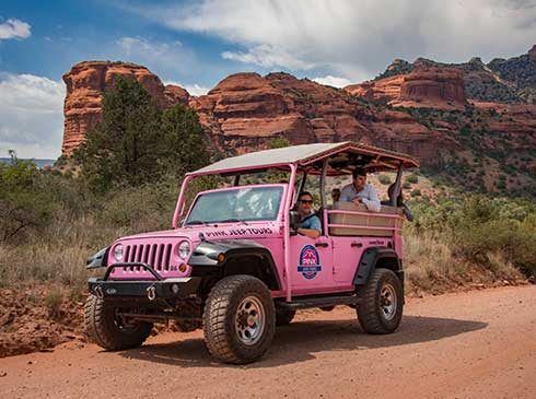 Medium-shot of Pink® Jeep® with guide and guests stopped on dirt road,  Sedona's red rock formations in background