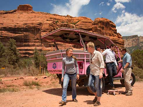 Tour guests exiting Pink® Jeep® vehicle with Sedona's large red rock formations in background