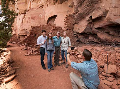 Pink® Jeep® guide taking photo of four guests standing by cliff dwellings at Honanki Heritage Site near Sedona