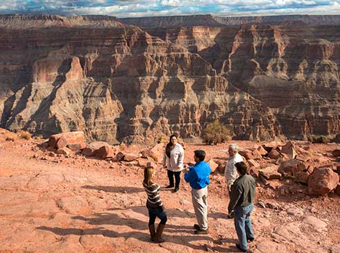 Pink® Jeep® tour guide explaining a view of the Grand Canyon West Rim for guests.