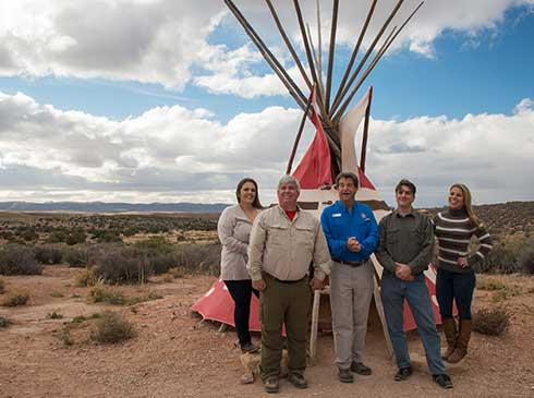 Group photo of Pink Jeep tour guide and guests in front of Native American tipi at Eagle Point, Grand Canyon West Rim