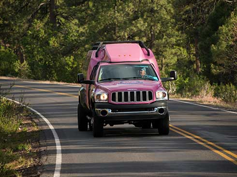Front view of Pink Jeep Tour Trekker driving up Oak Creek Canyon, Grand Canyon South Rim tour
