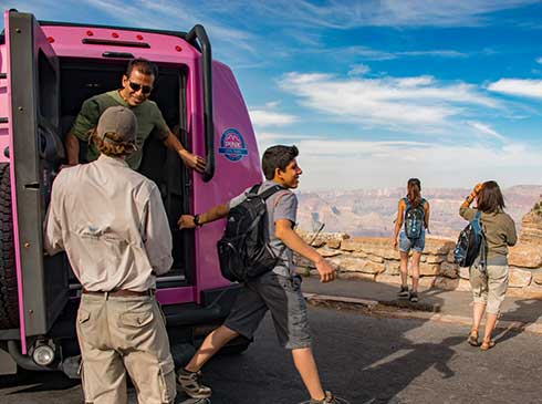 Grand Canyon South Rim tour guests exiting the back of Pink Jeep Tour Trekker with guide at canyon viewpoint.