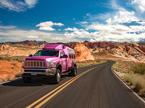Pink® Jeep® Tour Trekker driving up two-lane road in Valley of Fire State Park, NV