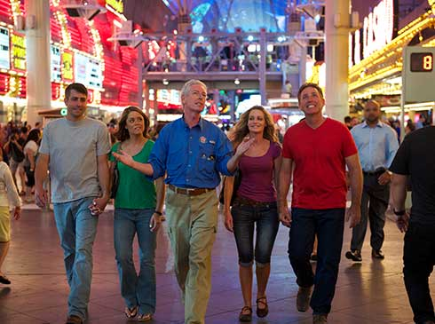 Pink® Jeep® tour guide and guests stroll under the lighted Fremont Street Experience, Downtown Las Vegas