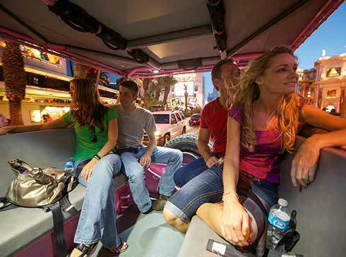 Guests riding in an open-air Pink Jeep while touring famous, must-see Las Vegas city landmarks