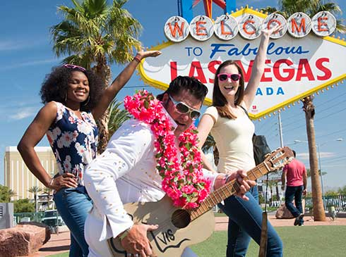 "Two Pink Jeep tour guests pose with Elvis in front of famous ""Welcome to Fabulous Las Vegas"" sign"