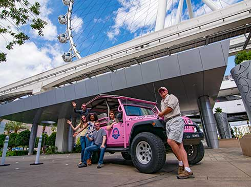 Guests pose for photo ops around an an open-air, Pink Jeep on the Las Vegas Sights and Sounds tour