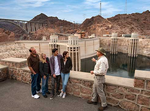 Pink Jeep guide explaining history of Hoover Dam to guests with view of dam spillway