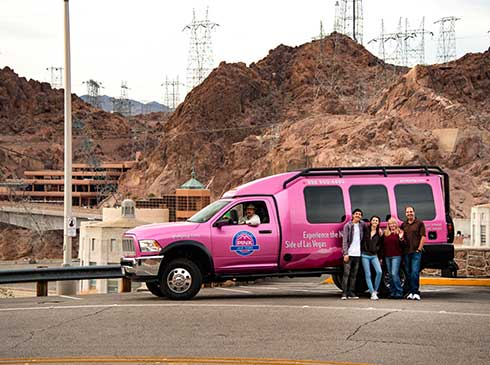 Group photo of tour guests in front of Pink® Jeep® Tour Trekker at Hoover Dam