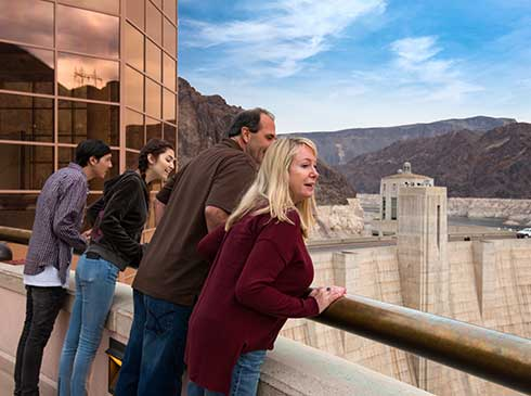 Four tour guests looking over rail at Hoover Dam in Las Vegas, Nevada
