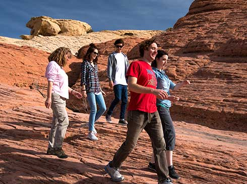 Pink Jeep tour guide and guests walking across jumbled sandstone in Red Rock Canyon National Conservation Area, NV