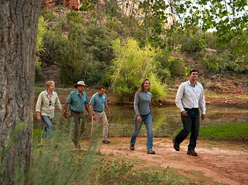 Pink® Jeep® guide and four guests walking along a heavily-vegetated trail past lower Oak Creek, near Sedona, AZ