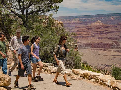 Pink® Jeep® guests and tour guide walking the Trail of Time from Yavapai Point to Grand Canyon Village