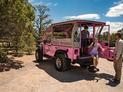 Two kids exiting the rear of a Pink® Jeep® Wrangler during the Trail of Time Tour with guide nearby