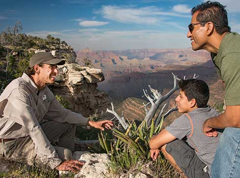 Pink® Jeep® guide explaining southwest desert vegetation to father and son with Canyon view in background