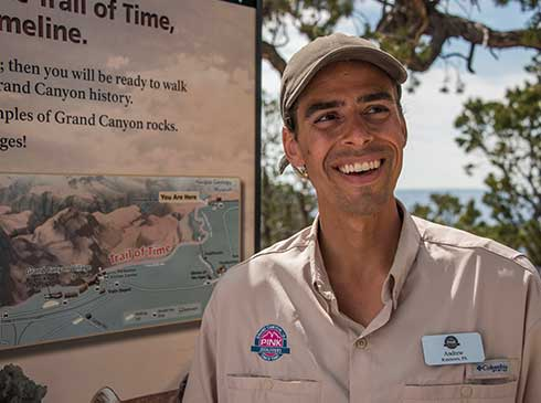 Pink® Jeep® certified guide standing by Trail of Time timeline map at Grand Canyon National Park