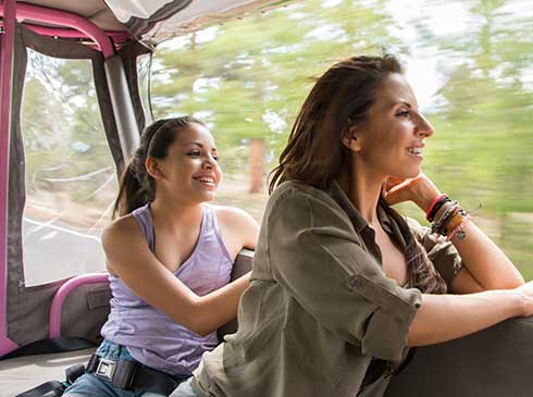 c324d31b Smiling mother and daughter looking at roadside views from a Pink® Jeep®  Wrangler