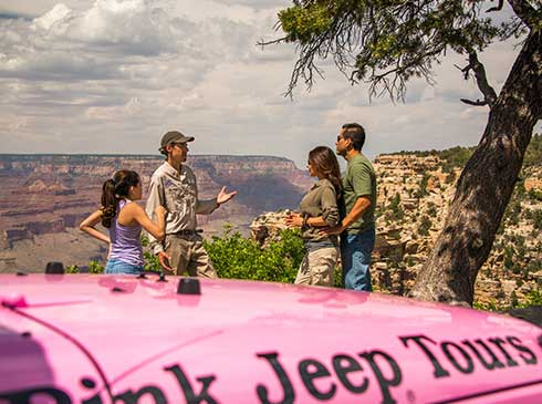 Pink Jeep guide talking with family of three overlooking the Canyon on Grand Entrance Tour