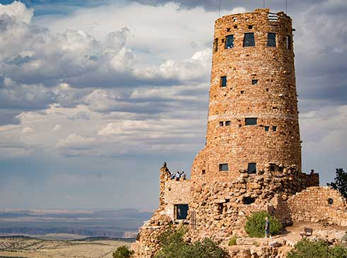Desert View Watchtower at Grand Canyon National Park with puffy blue sky in background