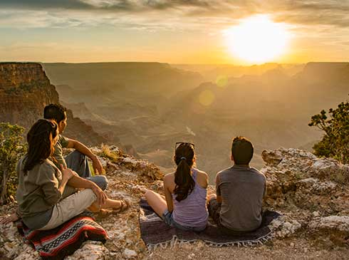 Family of four seated by rim of the Grand Canyon watching a golden sunset