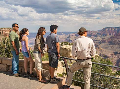 Pink Jeep tour guide and family of four looking out over the Grand Canyon