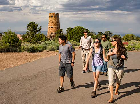 Pink® Jeep® guide leading a family on a walk, passing the Grand Canyon South Rim watchtower