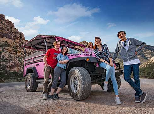 Fun group photo of tour guests posing on Pink Jeep Tour Trekker vehicle at Red Rock Canyon