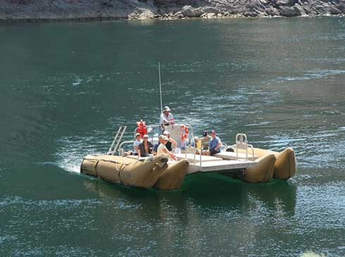 Pink Jeep tour guests floating on Colorado River below the Hoover Dam