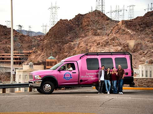 Group photo of tour guests in front of Pink Jeep Tour Trekker at Hoover Dam