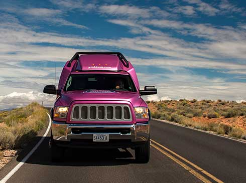 Front-end view of Pink Jeep Tour Trekker traveling through Mohave Desert en route to Grand Canyon West Rim