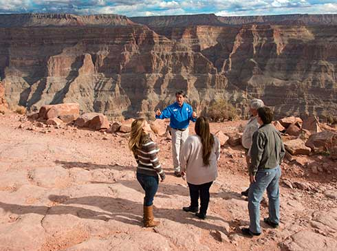 Pink® Jeep® tour guide talking with guests overlooking the Grand Canyon West Rim