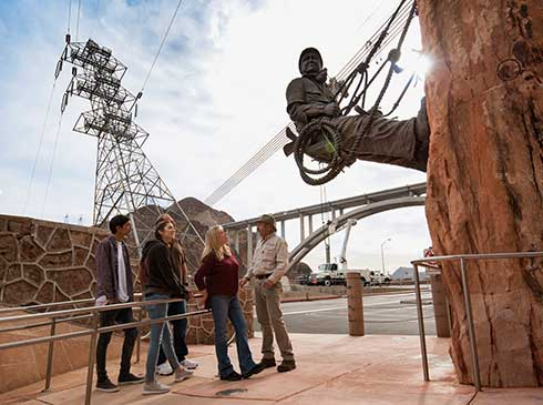 Group of Pink Jeep tour guests with guide looking at the bronze High Scaler Monument at Hoover Dam