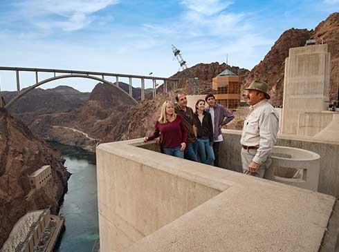 Guide talking to group at observation point on Hoover Dam with Colorado River below