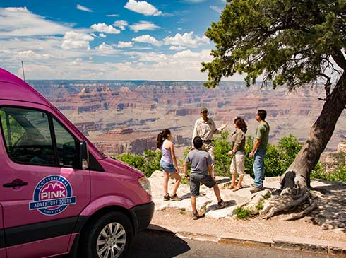 Pink Jeep interpretive guide talking with guests at Grand Canyon viewpoint, Mercedes Sprinter parked nearby