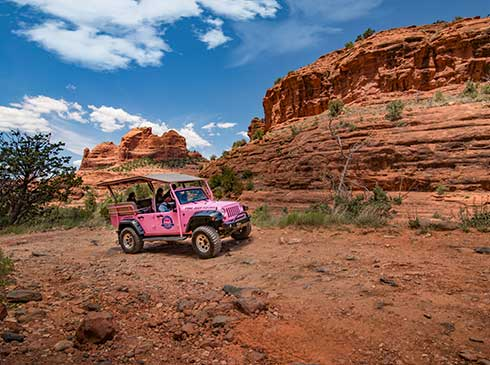 Custom Pink® Jeep® Wrangler with guests traveling the Broken Arrow Trail past large red rock formations