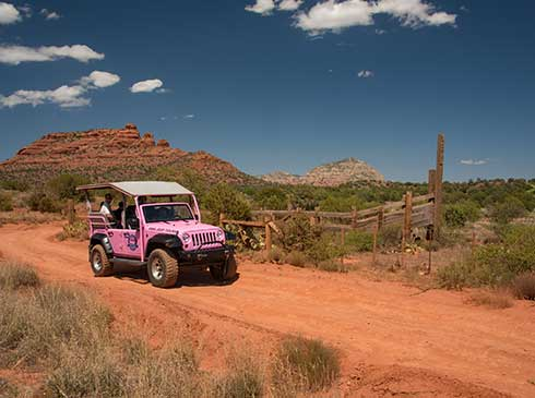 Open-air Pink Jeep travelling on red-dirt forest service road in Coconino National Forest, with Sedona's red rocks in distance